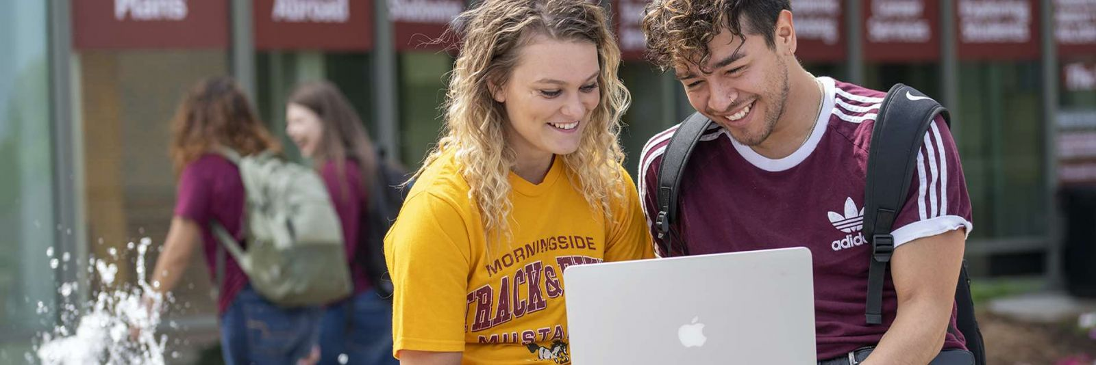 Students look at laptop outside by fountain