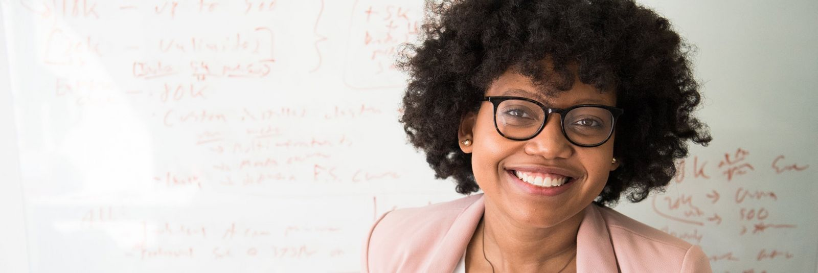 Teacher with glasses smiling in front of a white board