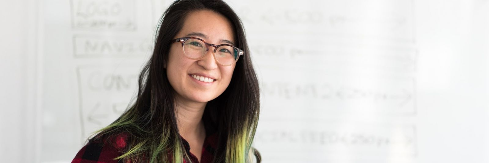 Smiling woman with glasses in front of a whiteboard