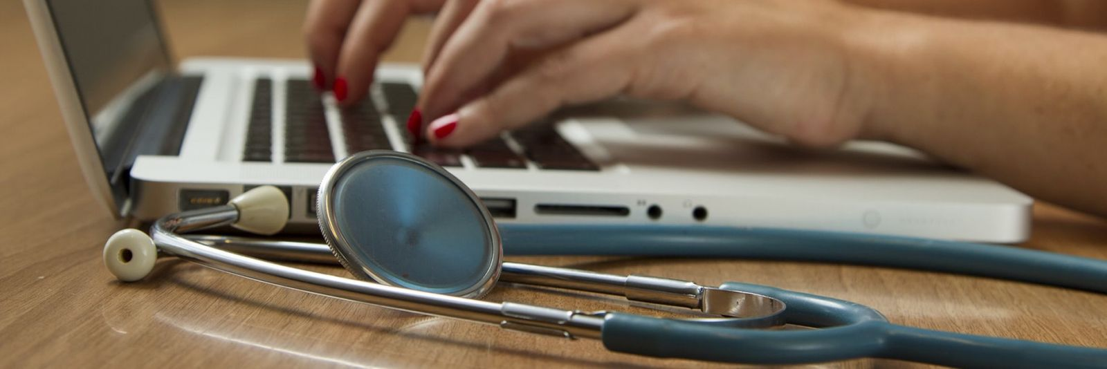 Hands typing on a laptop next to a stethoscope
