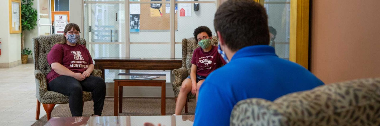 admissions counselor meeting with student with mask