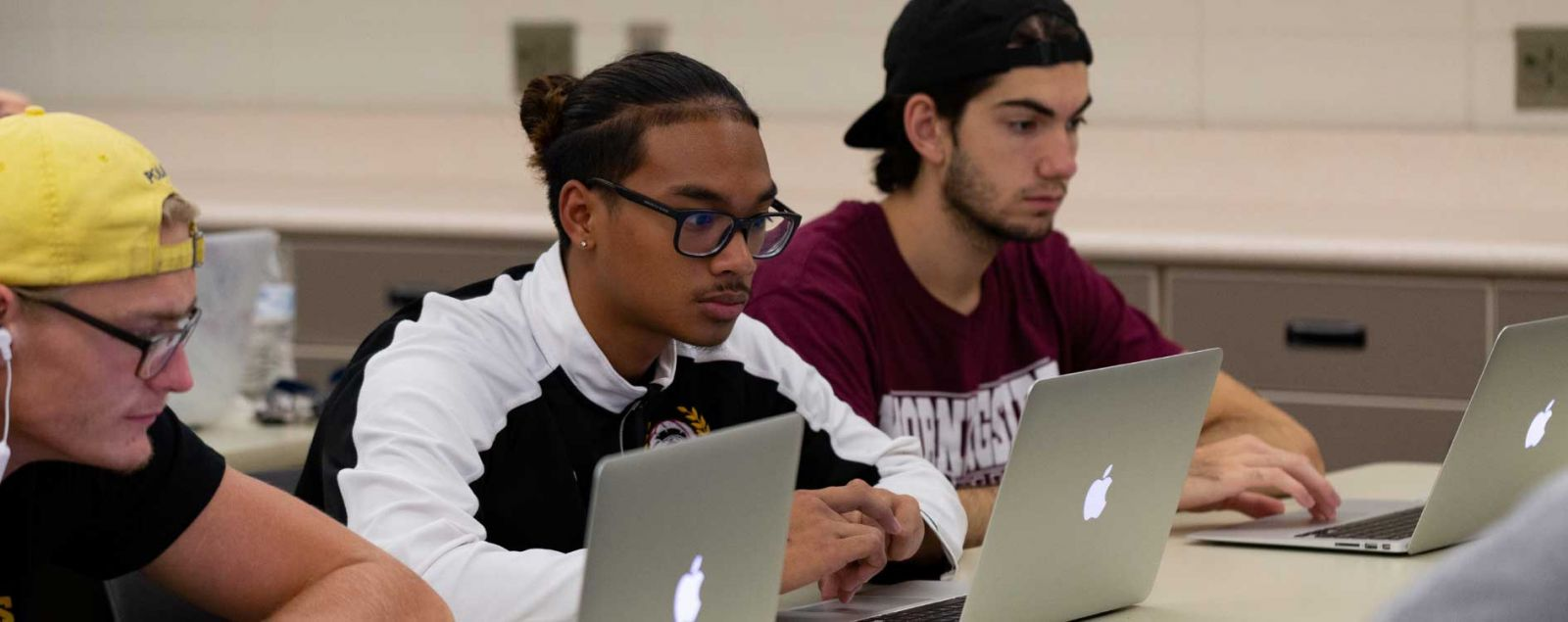 Student with Airpods on Laptop