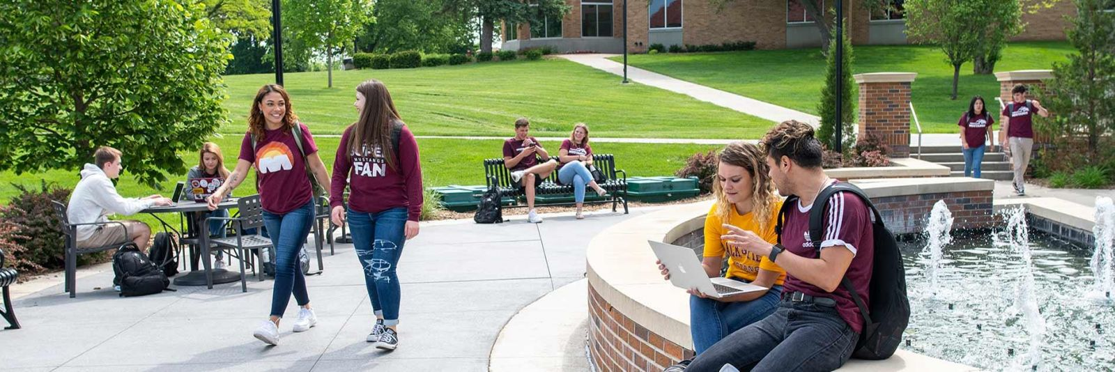 Morningside students walking outside in front of the fountain near the Krone Center on campus.