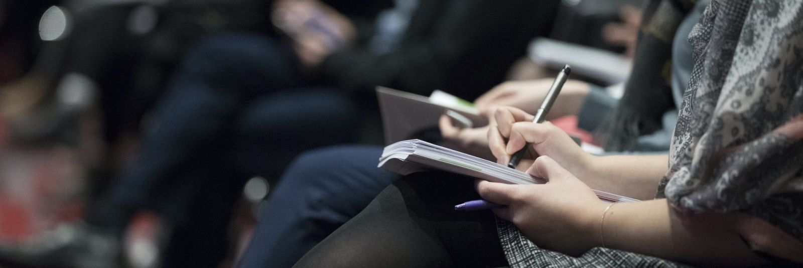 A woman holds a pen and writes notes during a conference