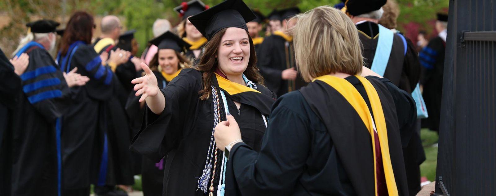 A graduating girl prepares to hug her mom