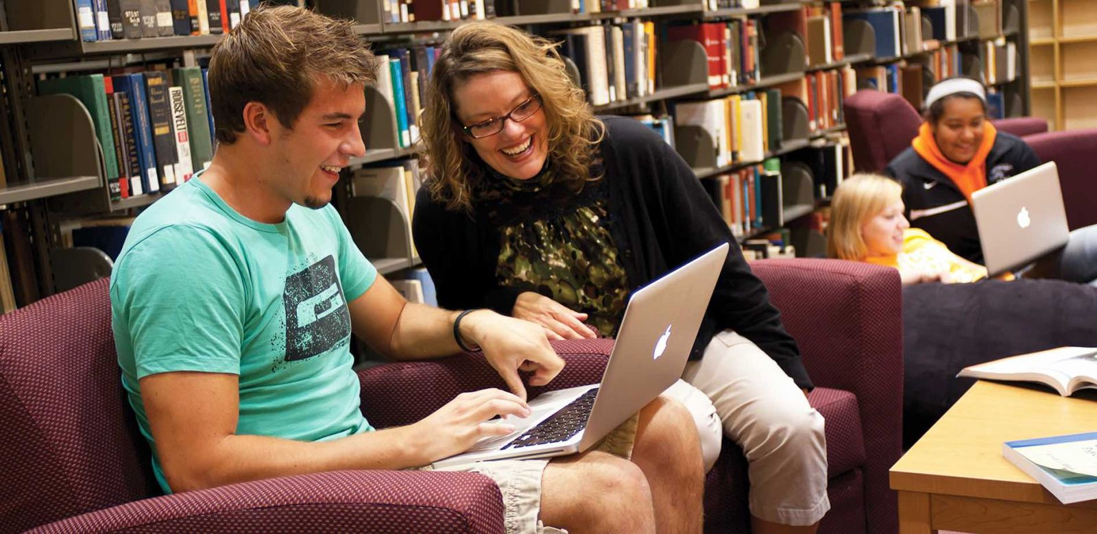 Leslie Werden laughing with a student in the library