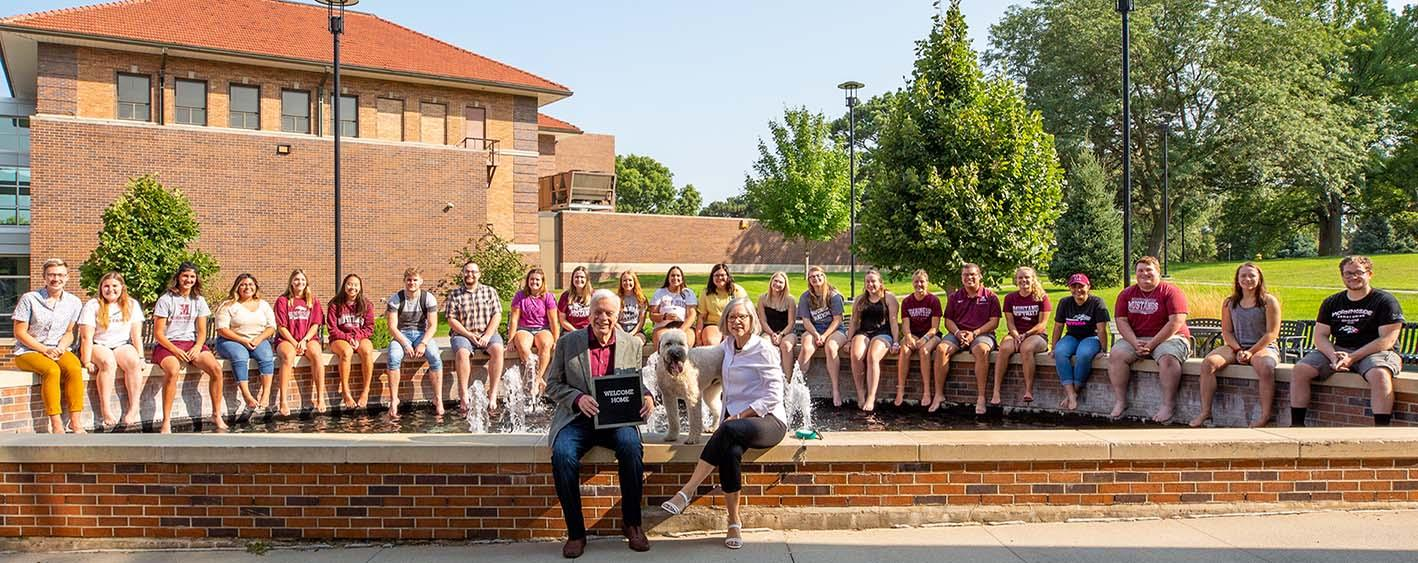 President John Reynders with his wife Robin and their dog Boomer sitting on a Morningside fountain with the 2021 WOO Crew