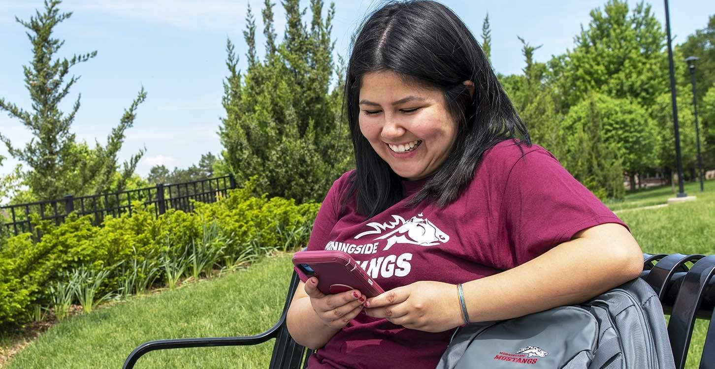 Student smiling at phone