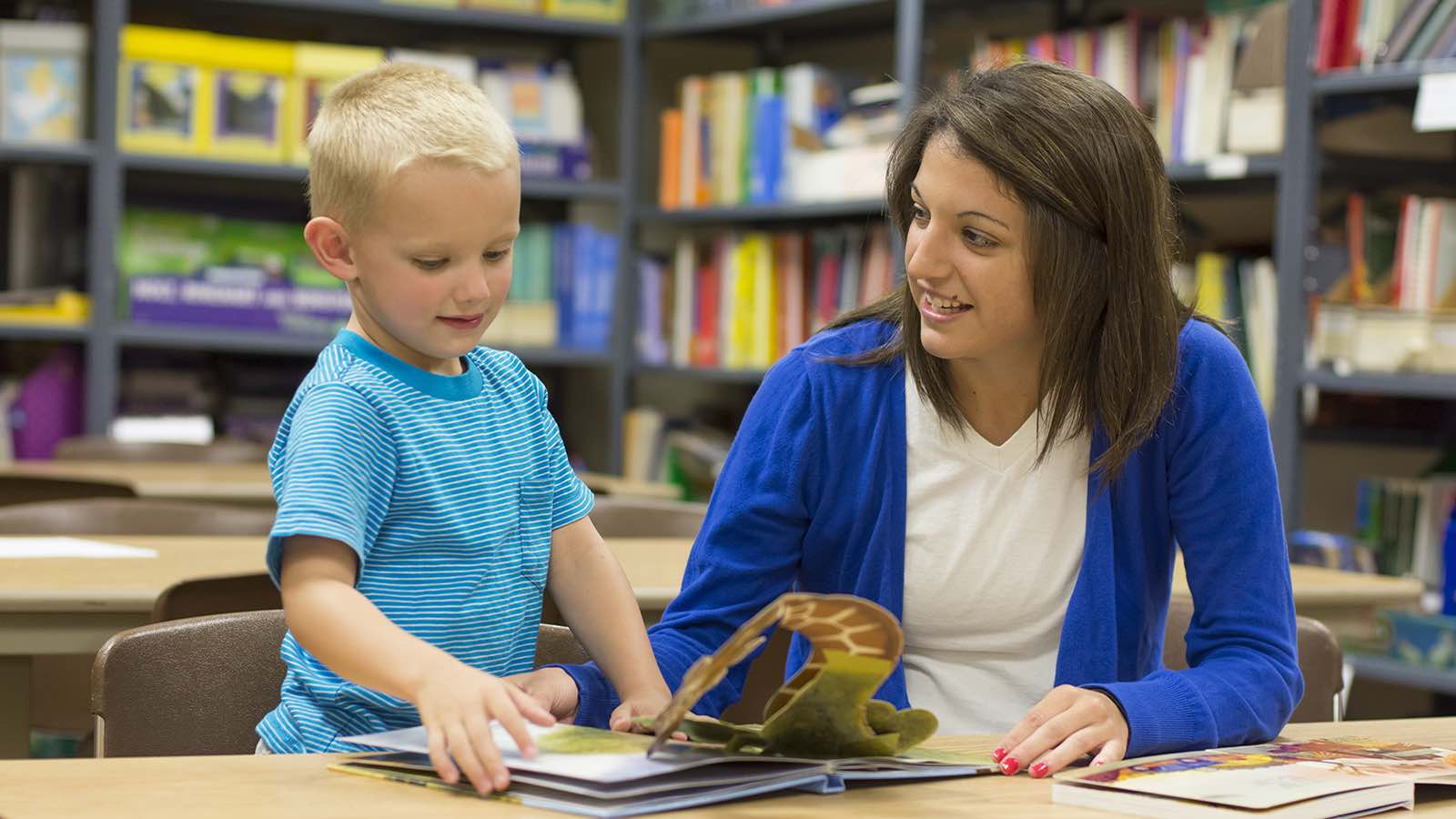 Female teacher reading a pop up book with a blonde elementary school student