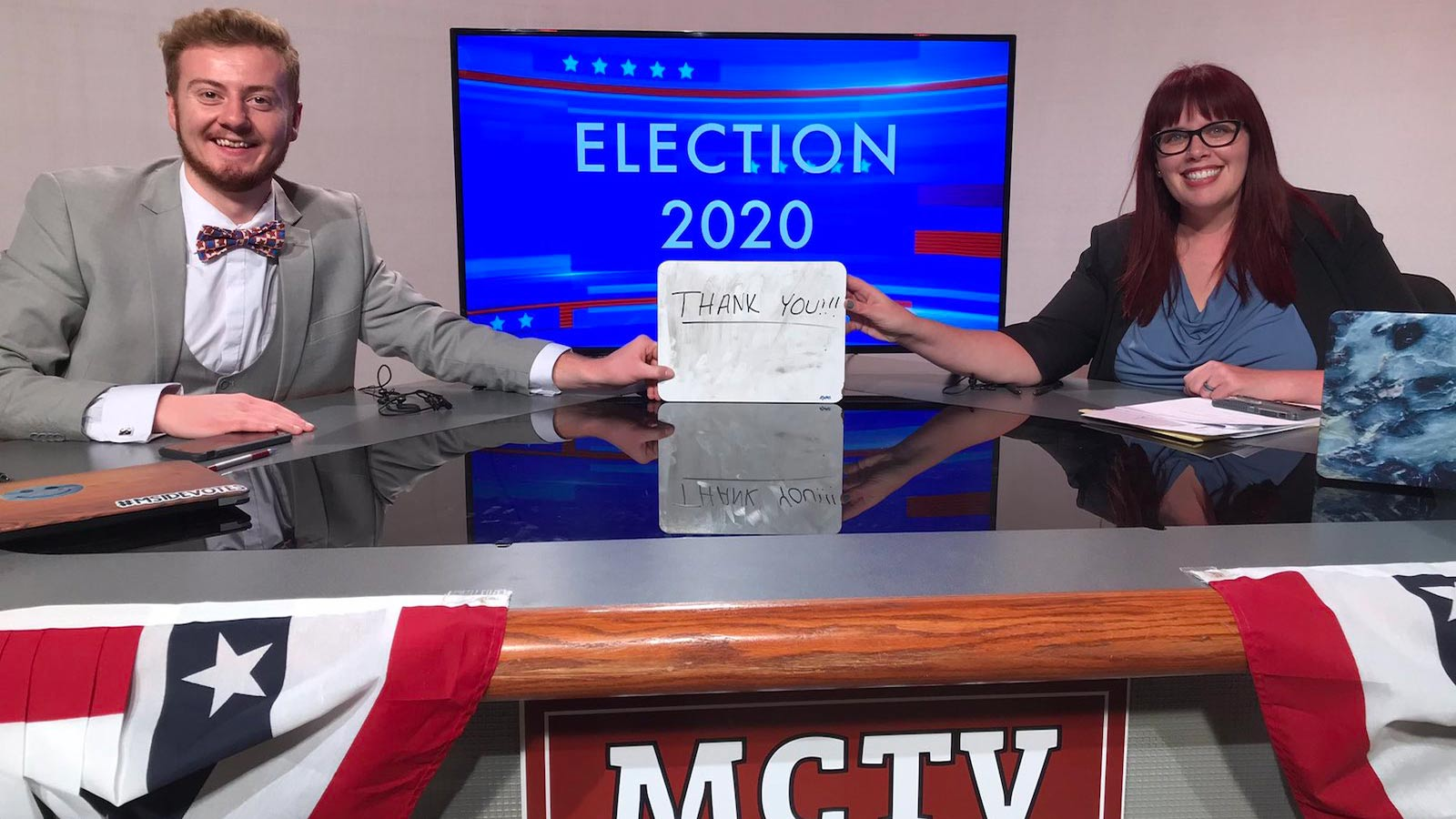 Morningside student Garrett Arbuckle and professor Val Hennings holding a Thank You sign during Election Night 2020