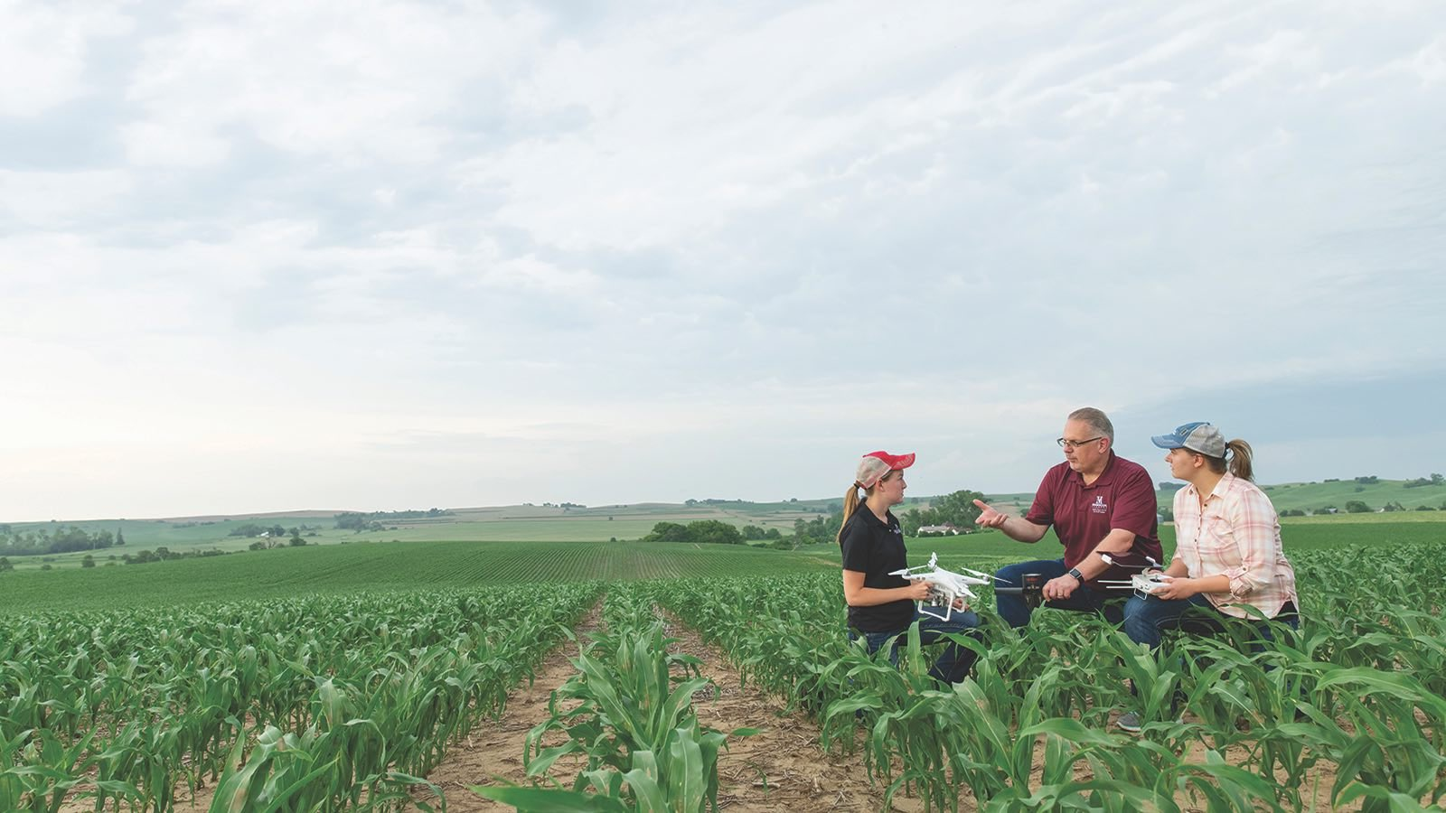 Agriculture students and faculty member Tom Paulsen examine a drone in the corn field