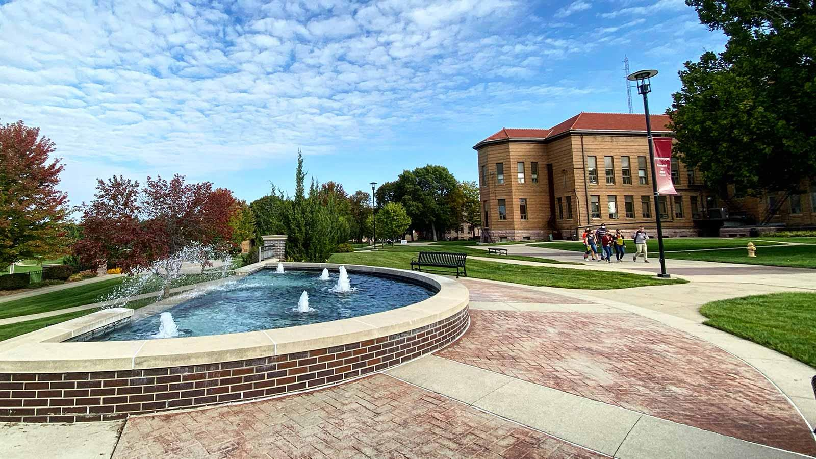 A group of visitors walks down the sidewalk in front of the fountain at Morningside