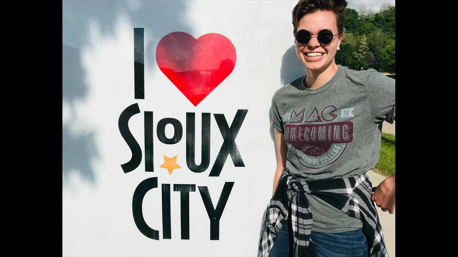Ally Hecht standing next to an I Heart Sioux City sign